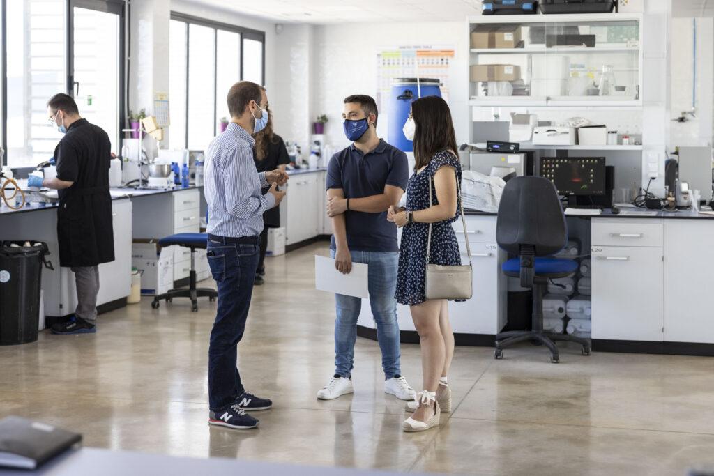 Aarón Martínez, director técnico de Zschimmer & Schwarz España, habla con el estudiante galardonado en los laboratorios de la empresa química